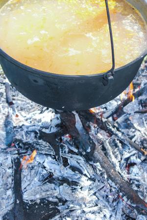 Fish soup boils in cauldron, food background