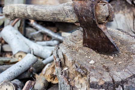 old rusty ax sticks out wooden deck Stockfoto
