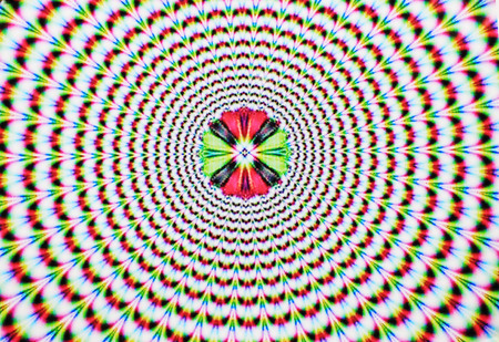 optical image: Digital abstract image with an explosion of blue red yellow green and purple producing an optical illusion of movement. Stock Photo