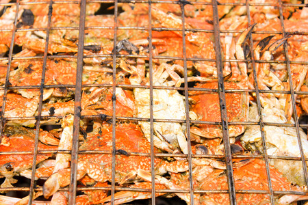 Grilled crab on flaming grill. Charcoal fire grill. Barbecue embers glowing in red fire. photo