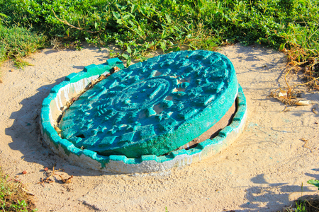 Old vintage sewer hatch painted with green paint
