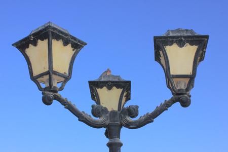 Old vintage metal street lamp on blue background
