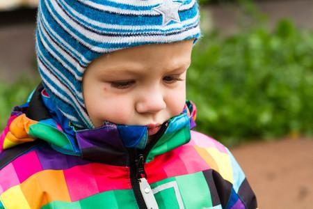 bambini pensierosi: a little boy walking on the street