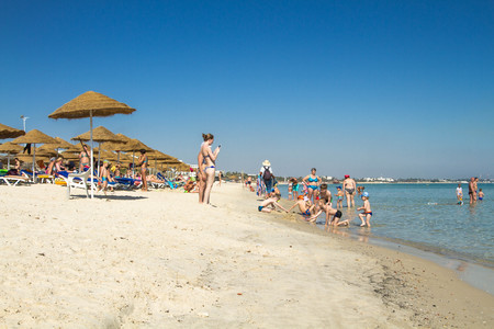 territory: June 25, 2017. Tunisia. People on the beach are swimming and sunbathing.