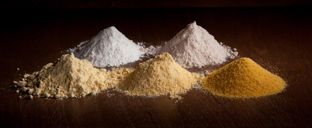maize flour: rice flour, sorghum and three different types of maize flour on a wooden background Stock Photo