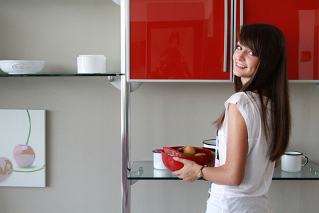 pureness: young woman in modern kitchen holding red bowl of fruit, dimple, smiling