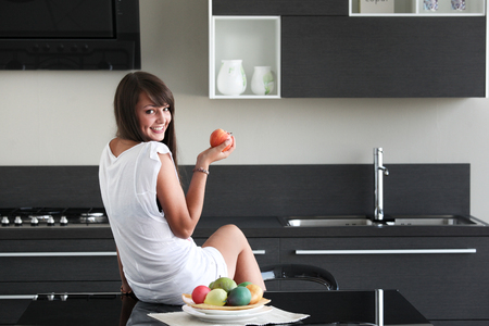 dimple: young woman in modern kitchen, sitting on table, holding apple, with fruit, smiling, dimple, looking over shoulder