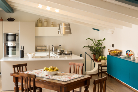 open plan: White and steel modern design open plan kitchen with turquoise accent color breakfront and wooden farm style table Stock Photo