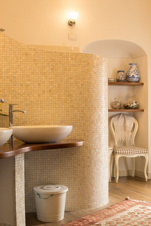 Elegant tiled bathroom in natural tones with design sinks and faucets, curved opalescent tile wall, niche with shelves, chair and vases
