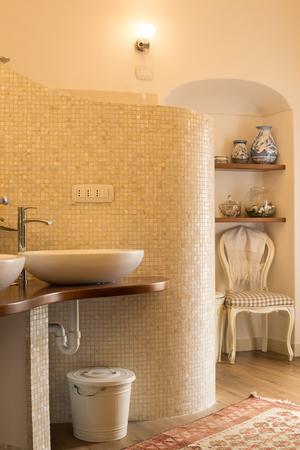 opalescent: Elegant tiled bathroom in natural tones with design sinks and faucets, curved opalescent tile wall, niche with shelves, chair and vases