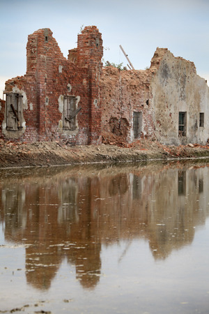 Crumbling wall of ruined brick building with water-filled rice field in foreground with reflection
