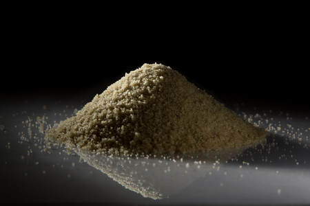 nutriments: Heap of fonio on black background, back lit
