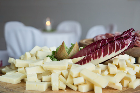 nutriments: cubes of cheese, radicchio leaf and kiwi on wooden cutting board, on catering buffet, sliced salami and table in background Stock Photo