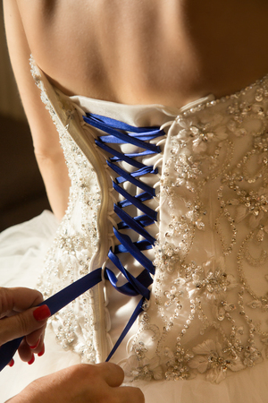 white strapless beaded bridal gown with blue corset lacing being laced, rear view Stock Photo