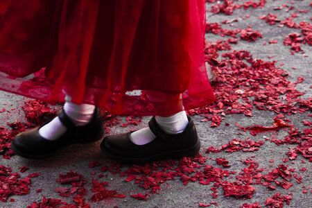Childrens feet standing on the ground, covered with red confetti