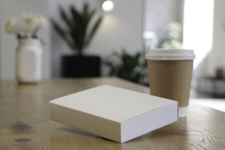 On the table is a mockup of a coffee cup and a white book. white box suitable for layout. Empty white background for design. White notebook. without text. Layout for overlaying your brand. Coffee house. Cafe background.