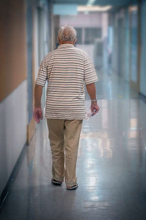 silhouette of an elderly man 70+ moving along the corridor of the hospital Stock fotó