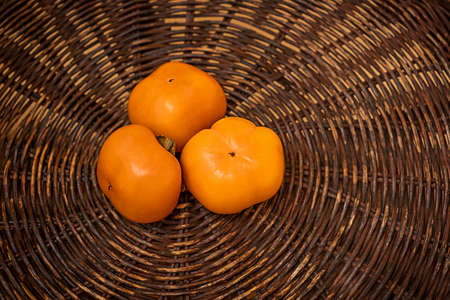 juicy frash orange date-plum. persimmon on wood texture. brown backgraund