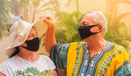 happy retirees wearing masks for safety. a retired elderly man looks under the old woman's hat to look at his wife. 免版税图像