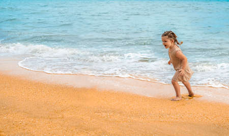 Cute baby on the beach. Happy girl runs away from the waves.