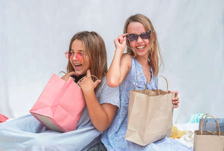 girls with glasses laugh. Children sort out shopping bags after shopping