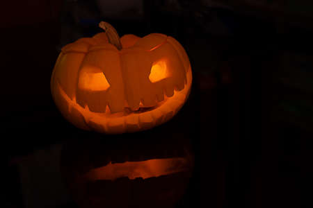 Halloween pumpkin Jack O lantern on black table background