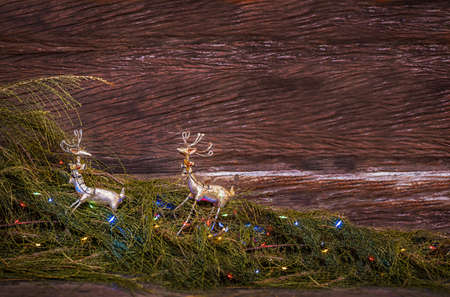 Christmas decorations. Deers toys on fir branches with lights on wooden background. the deer turns to the second.