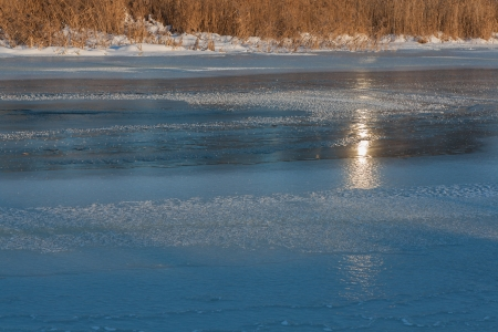 the sunset in the frozen river