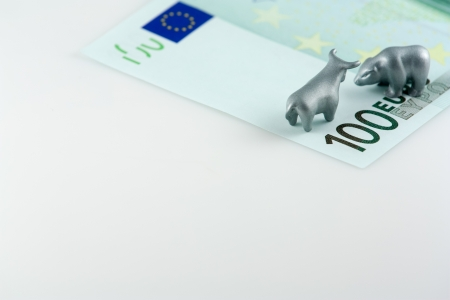 The photo shows the fragment of one hundred euro and metal bear and bull