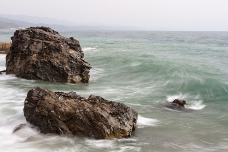 The photo shows the waves and rocks at sea.