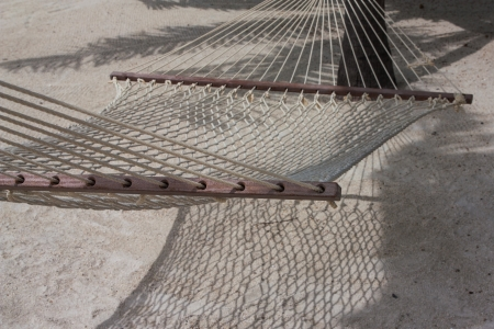 The photo shows a hammock on the beach. Stock Photo