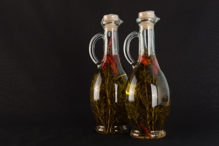 The photo shows the two glass jugs of olive oil on black. Stock Photo