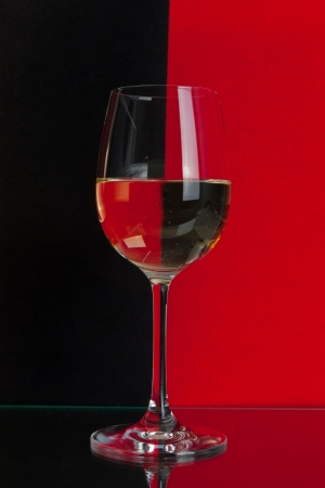 The photo shows the glass of wine on the background of two colors.