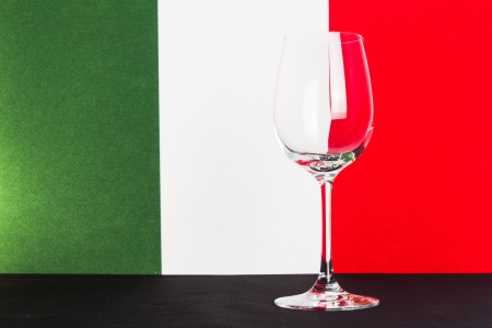The photo shows the glass of wine on the background of the Italian flag Stock Photo