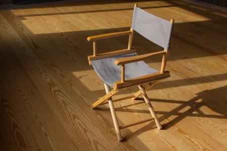 The photo shows the folding chair on the wood floor.