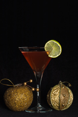 The photograph shows a chilled cocktail glass with a cocktail and christmas decorations. Stock Photo