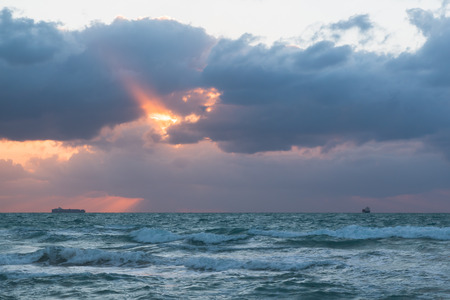 A ray of the rising sun breaks through the clouds in the ocean.