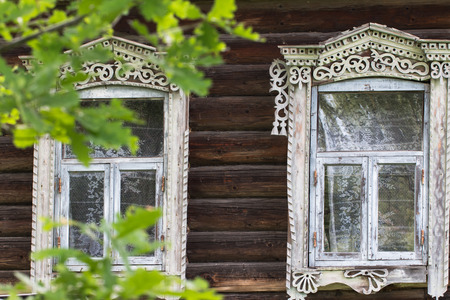 Two windows with carved architraves traditional Russian homes. Stock Photo