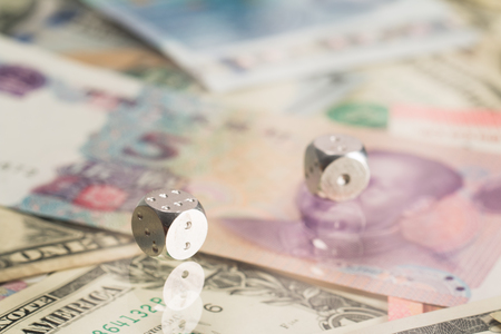 Metal dice lie on the background of paper money. Stock Photo