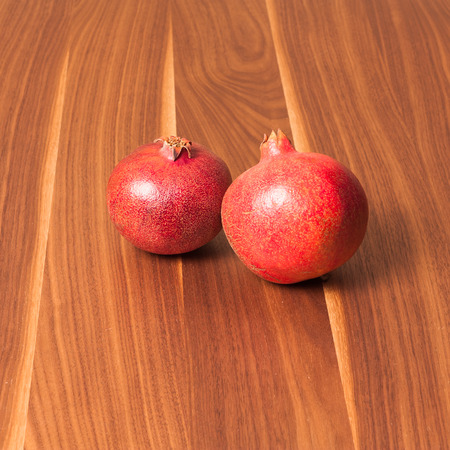 The photo shows two fresh pomegranates on the table. Stock Photo