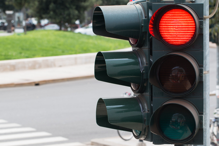 In the photo you see a city traffic light, a red light is on.