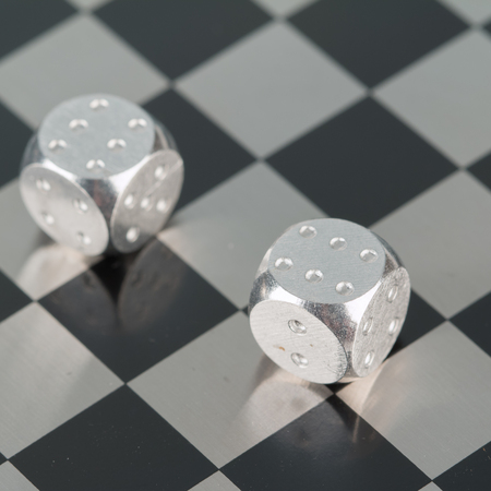 In the photo you see metal dice on a chessboard.