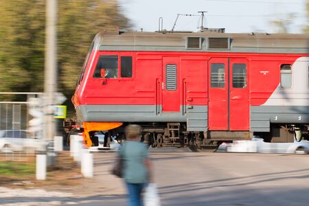 A local train of Russian Railways rushes past people standing at the railway crossing.