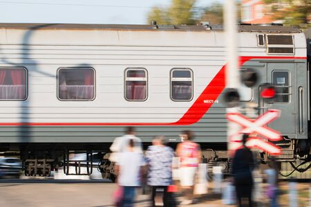 A long-distance train of the Russian Railways rushes past people standing at the railway crossing. 스톡 콘텐츠