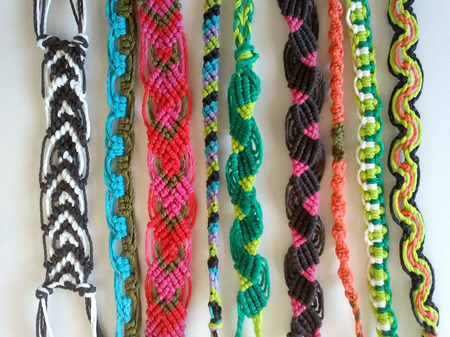 waxed: Nine bracelets made with waxed thread in a variety of colors with native macrame technique laid besides each other against white background
