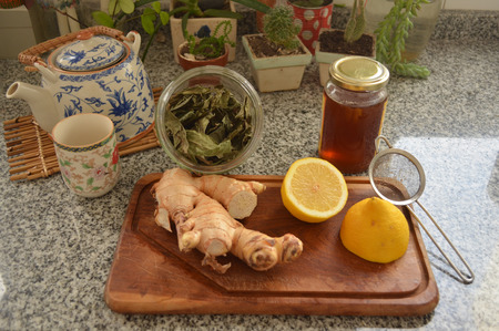 describe: Honey lemon ginger and green tea Presented with kitchen items to describe how to make a good winter tea