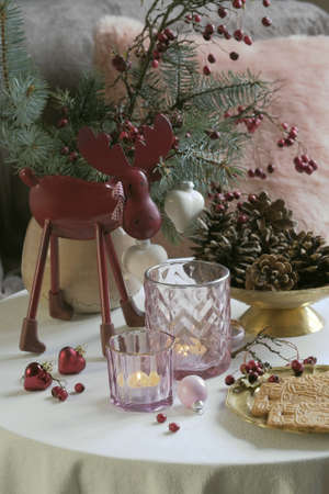 Christmas decorative figure elk made of metal and pine cones in a copper Patera. Two glass transparent candle holders for tealights. Spicy christmas cookies on a copper plate. Spruce and hawthorn branches in a beige ceramic vase
