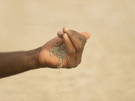 desertification: Desertification in the Sahel - African man holding some sand in the hand