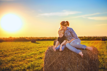 Mom and son at sunset sit in a field on a haystack and hug against the setting sun. Rural life, a walk in nature, a holiday in the countryside 写真素材