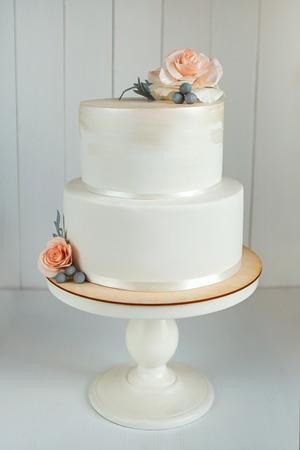 Laconic white wedding cake decorated with sugar flowers Reklamní fotografie - 100931625